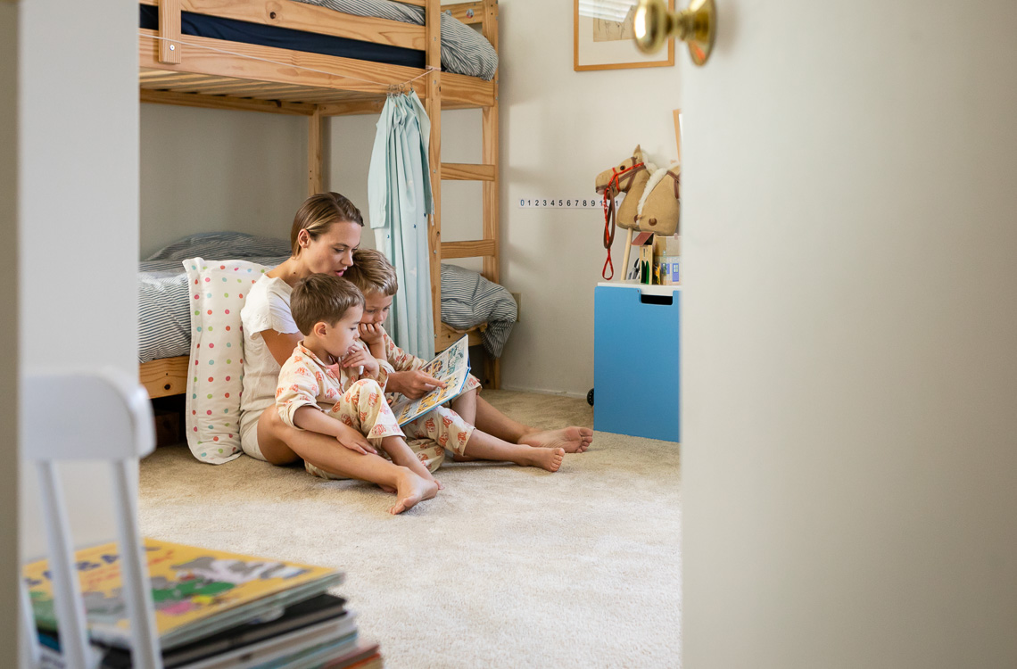 Mom sitting on the floor reading a comic book to her two boys by San Diego family lifestyle photographer Diane Hamacher