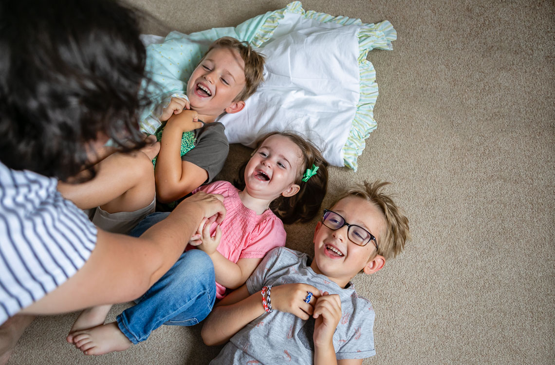 siblings laughing laying on the floor while mom is tickling them by San Diego family lifestyle photographer Diane Hamacher