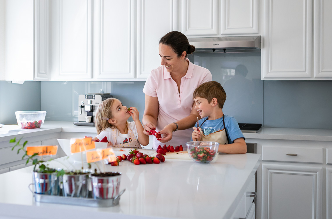 mom and her two kids preparing some strawberries in the kitchen by San Diego family lifestyle photographer Diane Hamacher
