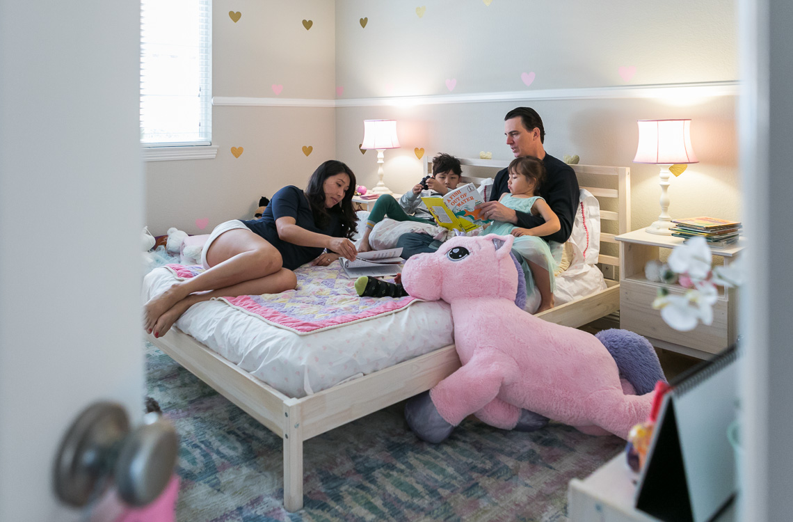 dad reading a book to his kids on the bed mom next to him by San Diego family lifestyle photographer Diane Hamacher