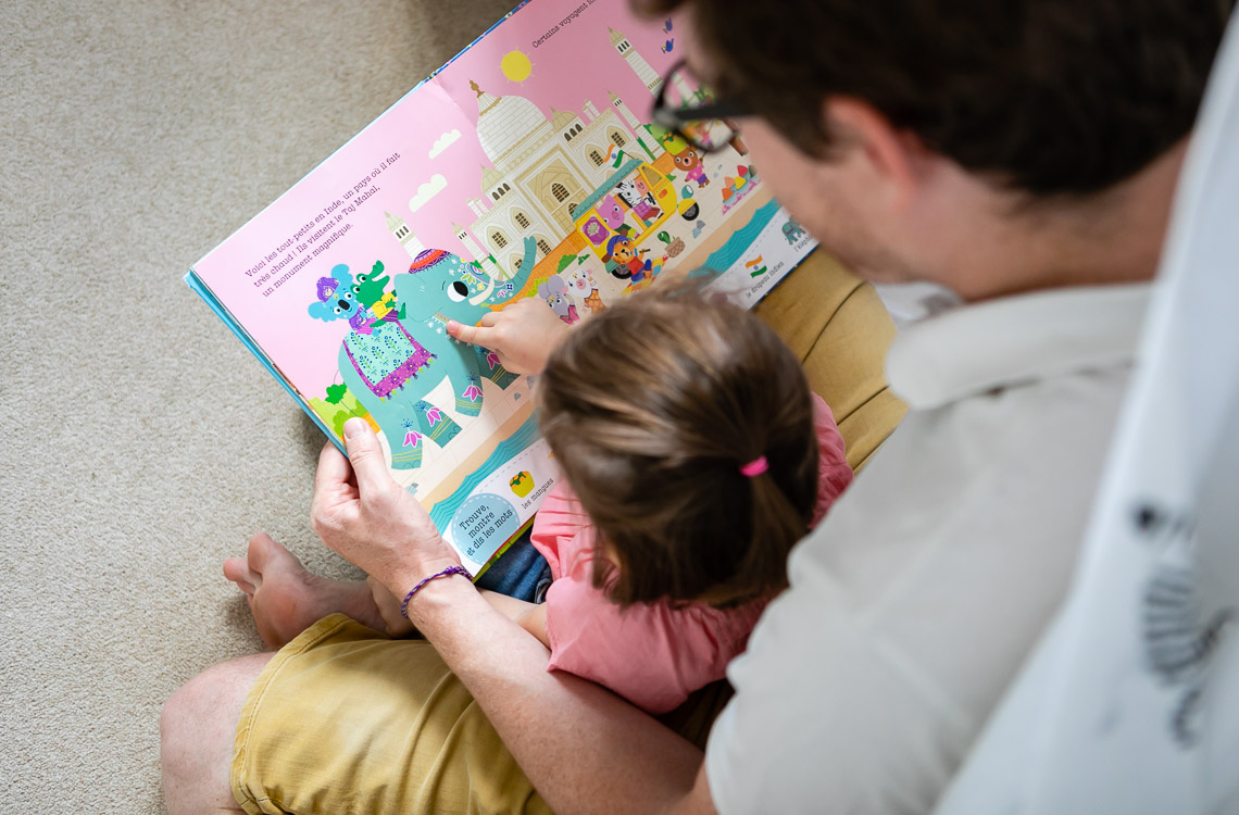 view from the top of a dad reading to his toddler girl by San Diego family lifestyle photographer Diane Hamacher