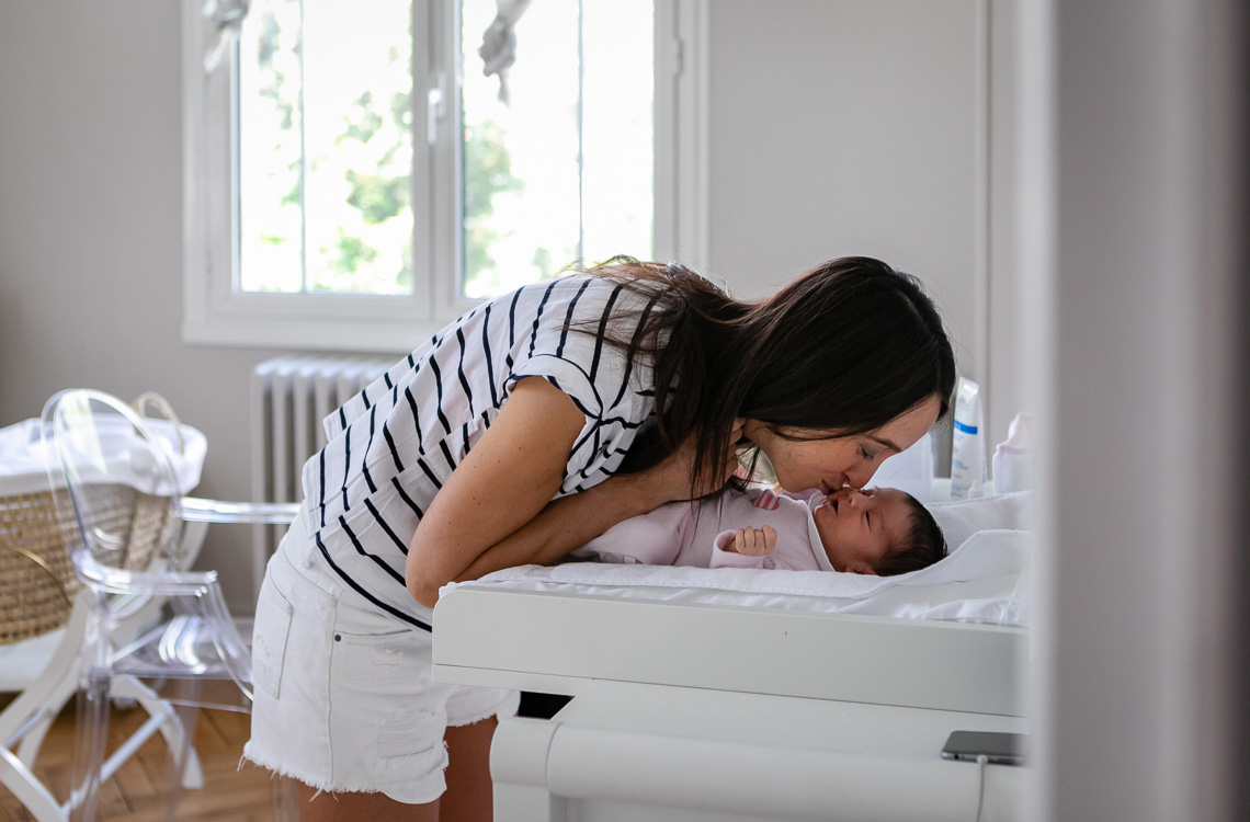 mom giving a kiss to her newborn baby laying on the changing table by San Diego family lifestyle photographer Diane Hamacher